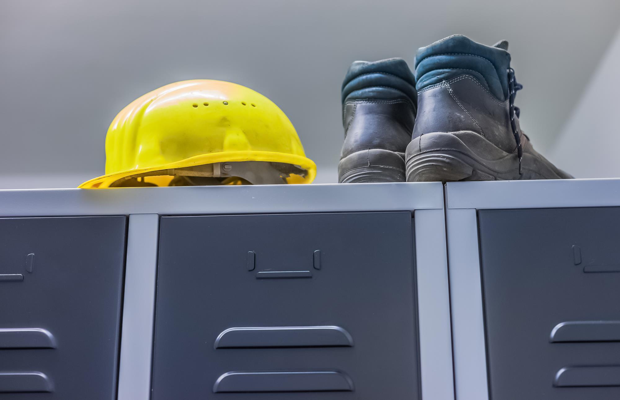 Buty robocze i kask leżą na metalowych szafkach w pomieszczeniu socjalnym dla pracowników.